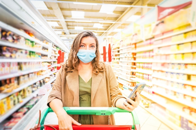 Kobieta nosząca maskę ochronną z listą kontrolną koszyka na zakupy w telefonie, robiąca zakupy podczas wybuchu pandemii i koronawirusa, stonowana