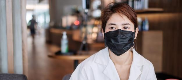 Kobieta nosząca ochronną maskę medyczną w kawiarni, zapobiegająca koronawirusowi lub chorobie koronawirusowej (covid-19). nowa koncepcja normalności i zdrowia