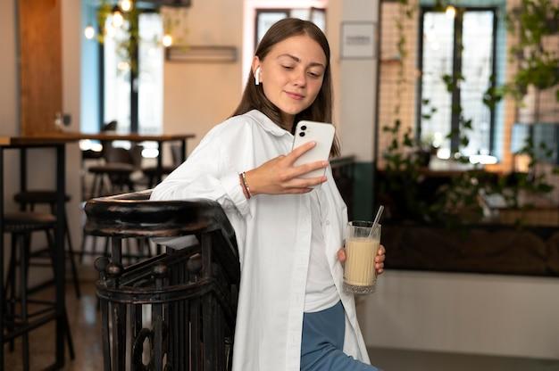 Kobieta nosząca słuchawki douszne podczas wybierania utworu ze swojego telefonu