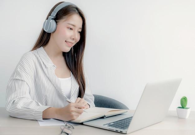 Kobieta notatki studenta oglądanie laptopa nauka online zajęcia wideokonferencja kurs edukacyjny z domu