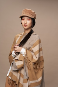 Kobieta o azjatyckim wyglądzie w tradycyjnej odzieży mody beżowym tle