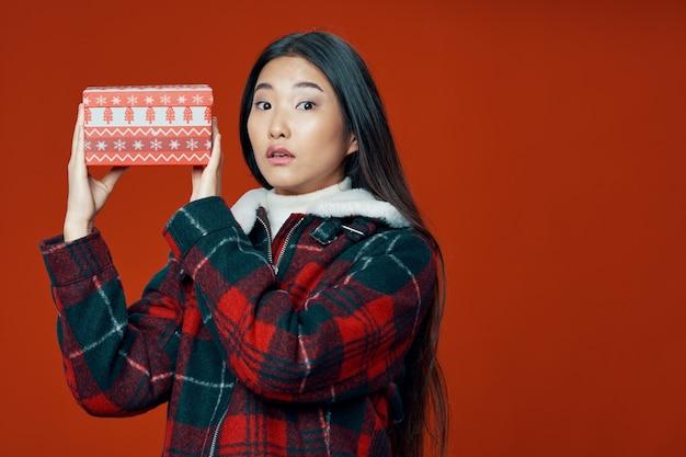 Kobieta o azjatyckim wyglądzie w zimowych ubraniach prezent na boże narodzenie na białym tle
