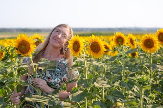 Kobieta o blond długich włosach stoi na polu słoneczników