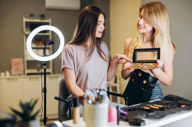 Kobieta o brązowych włosach wskazuje palcem wybrany kolor cienia do powiek. wizażystka i klientka wybierają kolor cieni do powiek.