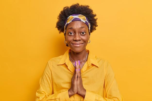 Kobieta o ciemnej skórze trzyma dłonie ściśnięte prosi o przysługę uśmiecha się delikatnie nosi koszulę i opaskę na żółto żywym kolorze