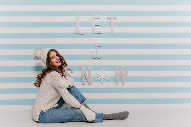 Kobieta o ciemnych kręconych włosach w świetnym nastroju pozuje siedząc w stylowych zimowych ubraniach pod ścianą z napisem let it snow