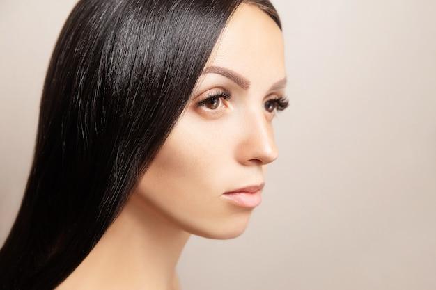 Kobieta o ciemnych, lśniących włosach i długich brązowych przedłużeniach rzęs