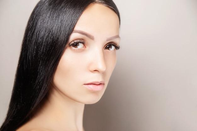 Kobieta o ciemnych, lśniących włosach i długich brązowych rzęsach. portret kobiecego piękna. przedłużanie rzęs, pielęgnacja skóry, uroda i spa
