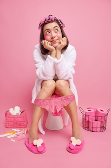 Kobieta o ciemnych włosach robi fryzurę za pomocą wałków nakłada płatki kosmetyczne pod oczy czuje się zrelaksowana siedząc na muszli klozetowej ma na sobie biały szlafrok koronkowe majtki na nogach pozuje w łazience