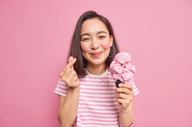 Kobieta o ciemnych włosach robi mini gest serca zjada pyszne lody gesty koreański jak znak wyraża pozy miłosne