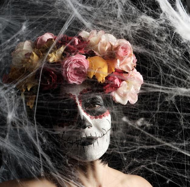 Kobieta o czarnych włosach jest ubrana w wieniec z różnokolorowych róż, a na jej twarzy robi się makijaż cukrowa czaszka do dnia zmarłych