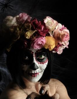 Kobieta o czarnych włosach jest ubrana w wieniec z różnokolorowych róż, a na jej twarzy wykonany jest makijaż sugar skull