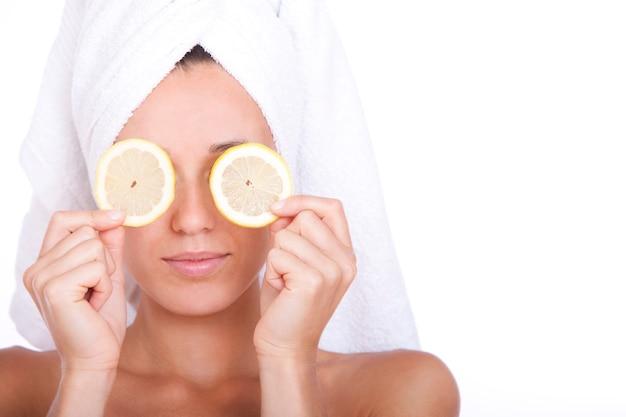 Kobieta o czystej twarzy trzyma dwa plasterki cytryny