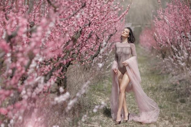 Kobieta o długich nogach idzie przez ogród z kocim chodem