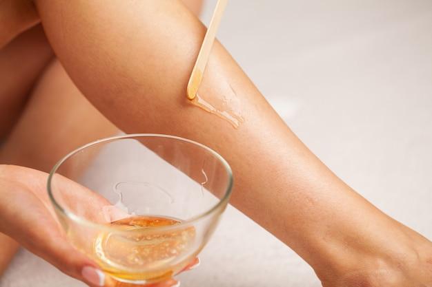 Kobieta o doskonałej skórze na nogach nałożyła wosk do usuwania włosów