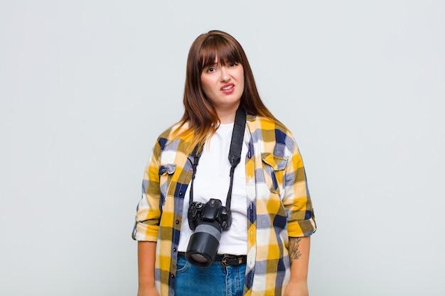 Kobieta o dużych rozmiarach czuje się zdziwiona i zdezorientowana, z głupim, oszołomionym wyrazem twarzy, patrząc na coś nieoczekiwanego