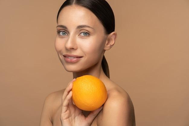 Kobieta o idealnej skórze twarzy, uczesanych włosach, trzymającej pomarańcz.