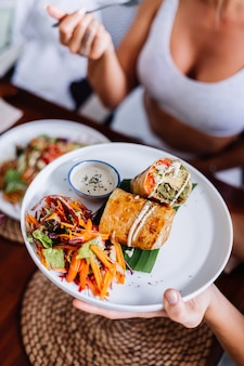 Kobieta o kolorowe zdrowe wegańskie wegetariańskie posiłek sałatka w letniej kawiarni naturalnym świetle dnia