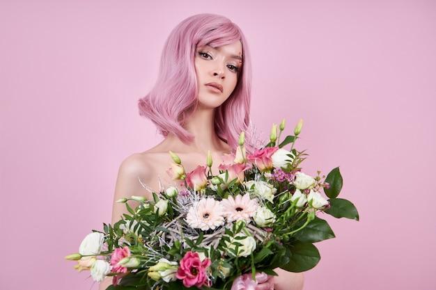 Kobieta o mocnych, różowych włosach trzyma w dłoniach bukiet pięknych kwiatów. naturalnie farbowane włosy piękny makijaż, mocne odrosty