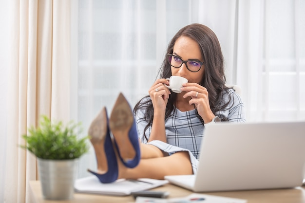 Kobieta o nogi, picie kawy, przerwę w biurze.