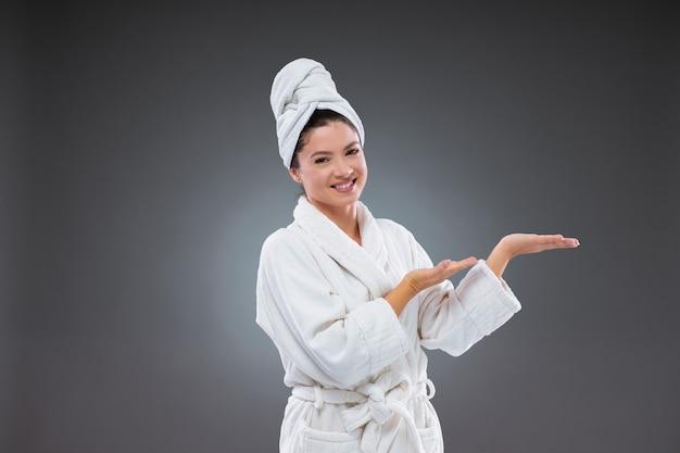Kobieta o pięknej i czystej twarzy w białym ręczniku i szlafroku oraz eleganckich ruchach wskazuje kierunek