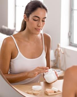 Kobieta o relaksujący dzień i używanie kremu do ciała