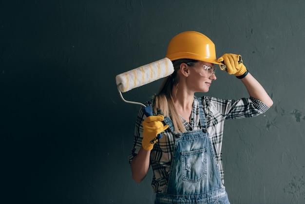 Kobieta o silnej woli w hełmie budowlanym, rękawicach, okularach i kombinezonie zajmuje się naprawami i pracami budowlanymi w domu. koncepcja silnej i niezależnej kobiety