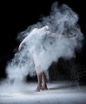 Kobieta o sportowej sylwetce tańcząca w chmurze rozsypanej białej mąki na czarnym tle, tancerka ubrana w czarne body