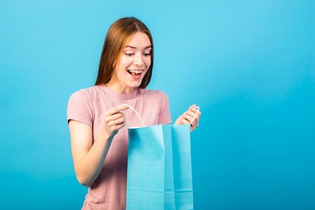 Kobieta o średnim ujęciu patrząc na zakupione przedmioty
