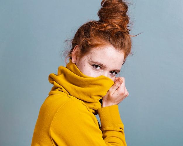 Kobieta o średnim ujęciu zakrywająca twarz kapturem