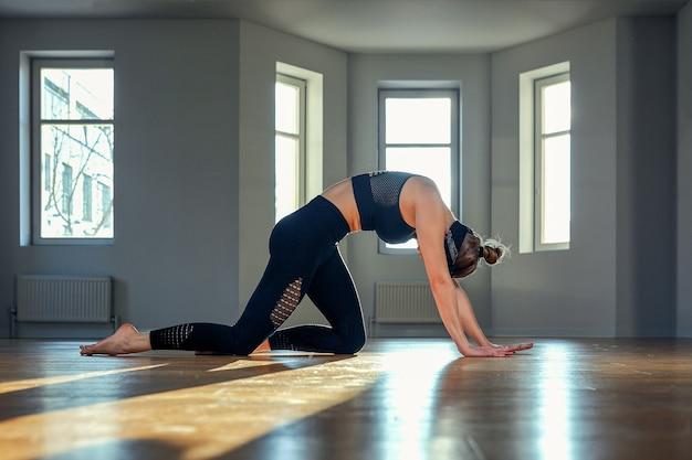 Kobieta o świcie ćwiczy jogę w sali fitness