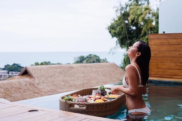 Kobieta o tropikalne zdrowe śniadanie w willi na pływającym stole