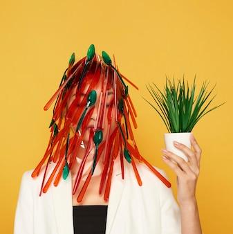 Kobieta o twarzy zakrytej czerwonymi i zielonymi łyżkami i widelcami