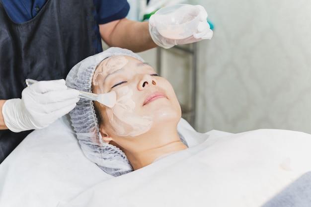 Kobieta o zabieg na twarz w spa z kosmetyczką stosując maskę na twarz pani.