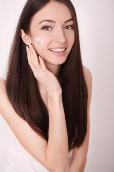 Kobieta o zdrowej twarzy stosowania kremu kosmetycznego pod oczami