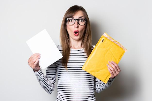Kobieta o zdziwionej twarzy wyjmuje list lub zawiadomienie z papierowej koperty