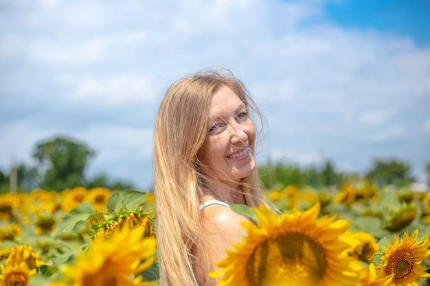 Kobieta o złotym kolorze włosów uśmiechnięta na polu z kwiatami słonecznika