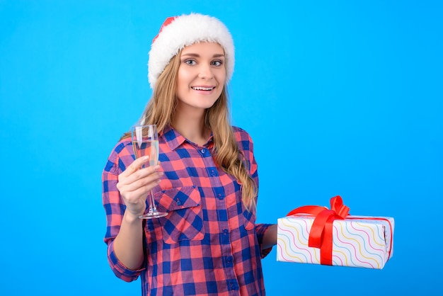 Kobieta obchodzi boże narodzenie trzymając kieliszek szampana i pudełko na prezent