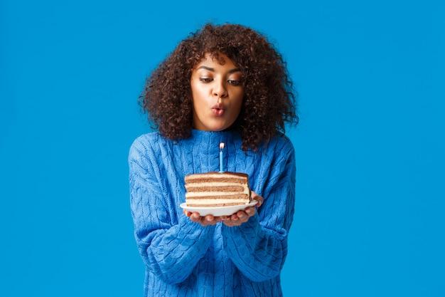 Kobieta obchodzi urodziny na zimę w kręgu rodzinnym. urocza i szczęśliwa afroamerykańska dziewczyna