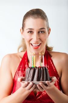 Kobieta obchodzi urodziny z ciasta i świece
