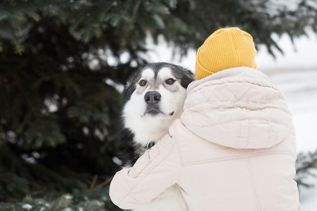 Kobieta obejmująca młody alaskan malamute dogin winter forest