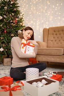Kobieta obejmująca pudełko prezentowe, siedząc między wieloma prezentami w świątecznym życiu udekorowanym