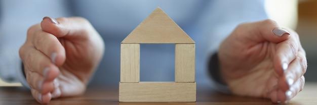 Kobieta obejmujące drewniany dom z jej ręką zbliżenie. pojęcie ubezpieczenia nieruchomości