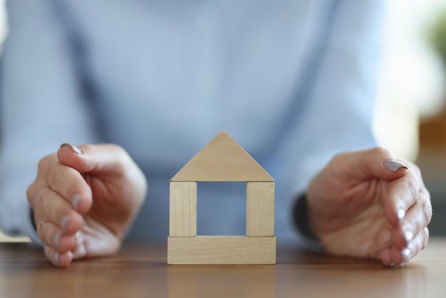 Kobieta obejmujące drewniany dom z jej ręką zbliżenie