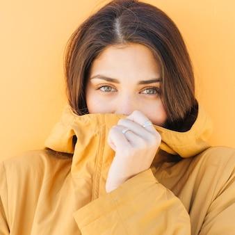 Kobieta, obejmujące jej usta kurtka patrząc na kamery