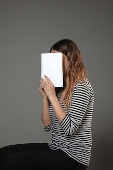 Kobieta obejmujące twarz z książki podczas czytania na szarej ścianie. świętowanie, edukacja, sztuka, cieszenie się nową koncepcją postaci.