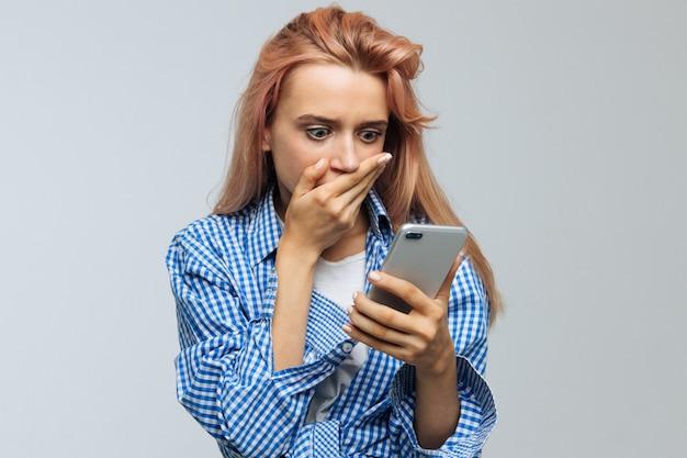 Kobieta obejmujące usta ręką, patrząc na jej telefon