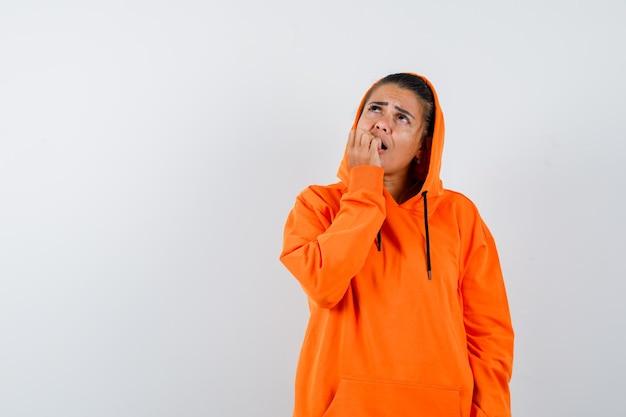 Kobieta obgryzająca paznokcie w pomarańczowej bluzie z kapturem i wyglądająca na przestraszoną