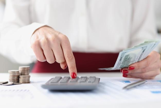 Kobieta oblicza na kalkulatorze i trzyma gotówkę w ręku w koncepcji usług księgowych przy stole roboczym