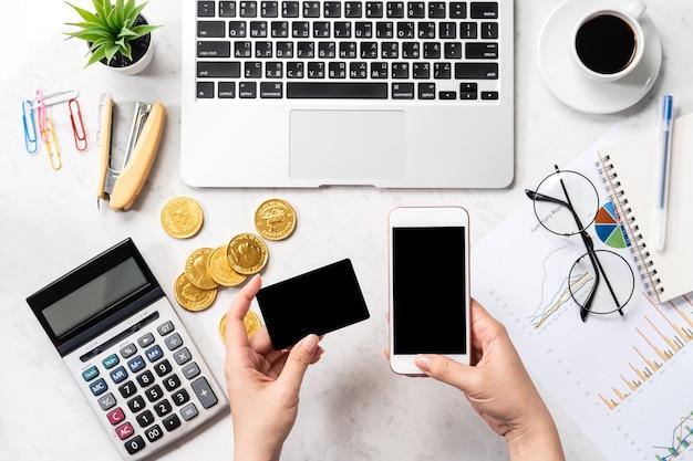 Kobieta oblicza opłatę, zysk i dokonuje płatności online na nowoczesnym marmurowym stole biurowym, makieta, widok z góry, miejsce do kopiowania, układanie na płasko